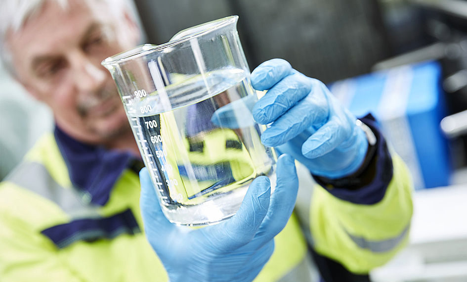 WESSLING employee examines water sample